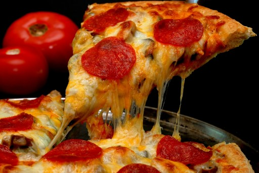Slice of pepperoni pizza being removed from whole pie with tomatoes in background. Isolated on black.